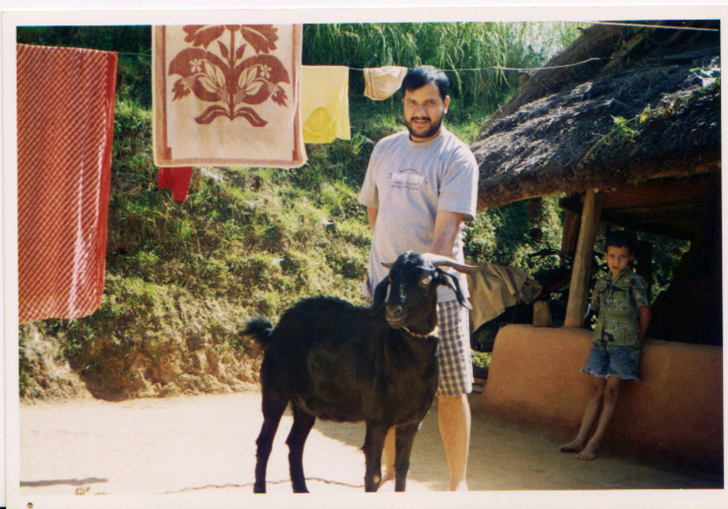My father holds a goat raised to slaughter for the Nepali festival Dashain in the early 1990s.